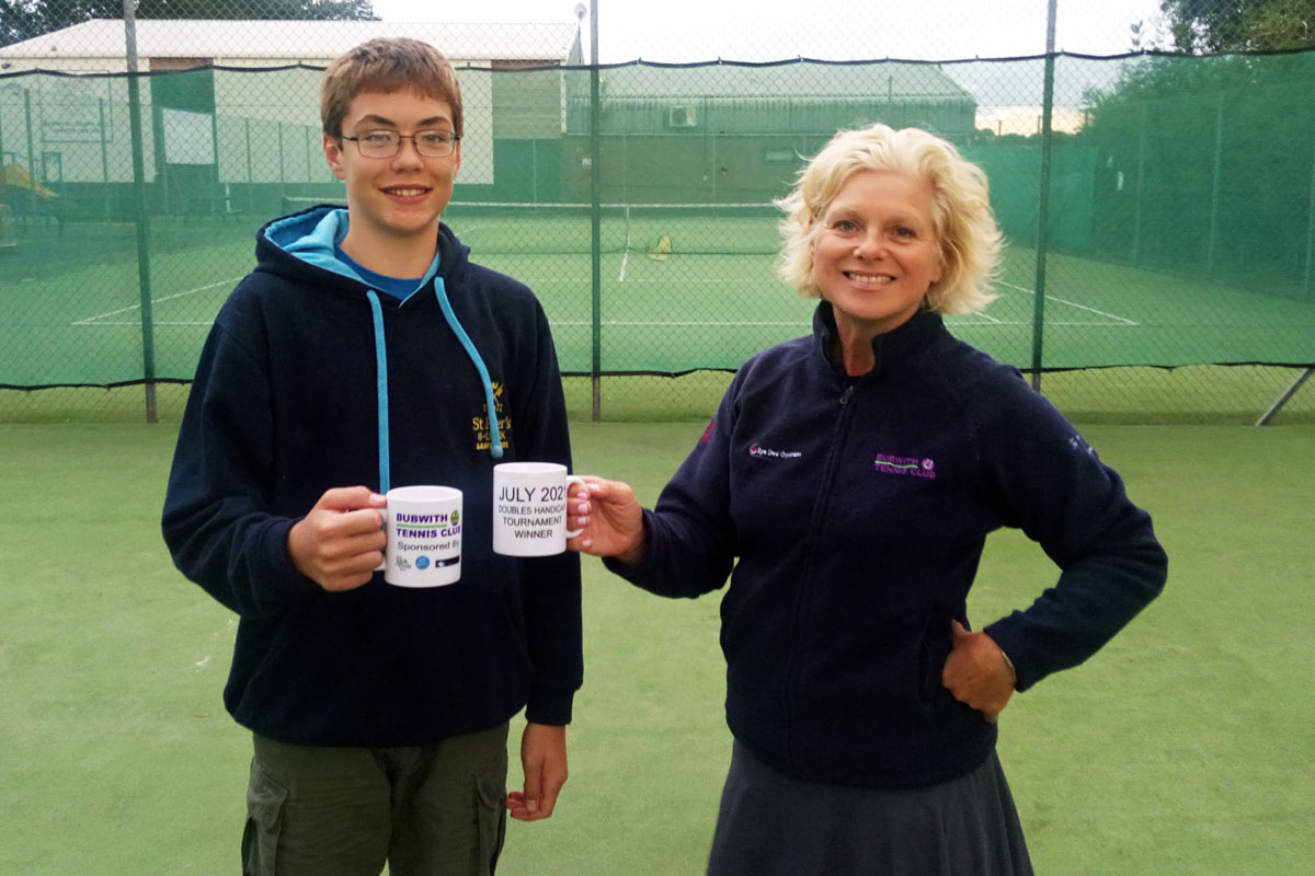 Doubles handicap tournament winners with their prize mugs